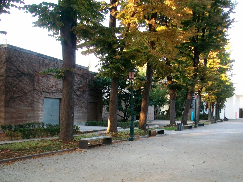 Figure 3.1: Main avenue of the Giardini, looking northeast, and showing the Spanish pavilion in the foreground, the Belgian and Dutch pavilions behind the trees, and the Central Pavilion (the main exposition venue) at the far right. Photograph: Joel Robinson.